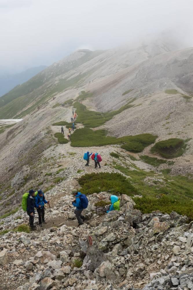 三国境で休憩する登山者