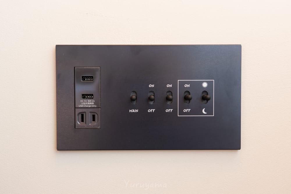 エースホテル京都室内の照明スイッチとUSBコンセントの画像